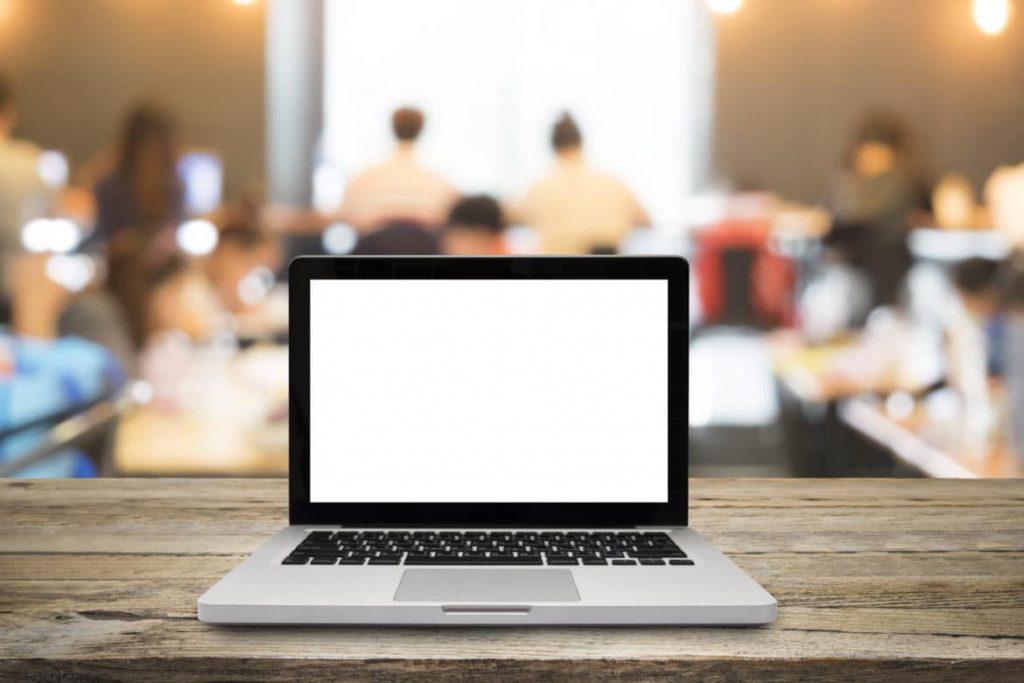 Ecran d'ordinateur avec en arrière-plan un groupe de personnes en session de formation
