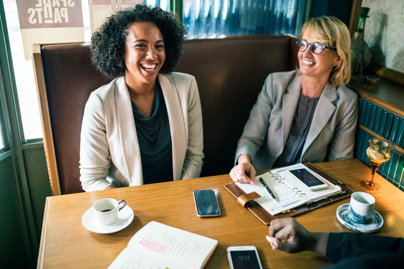 2 femmes souriantes en train de travailler